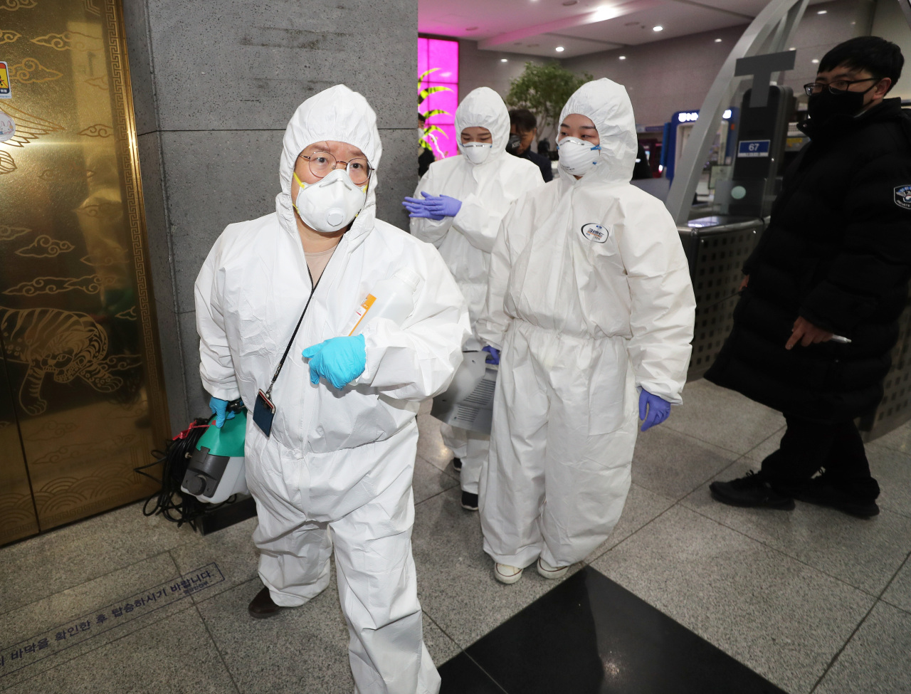 Officials enter the Ministy of Health and Welfare in Sejong on Saturday to disinfect the building where a public servant was diagnosed with COVID-19. Yonhap