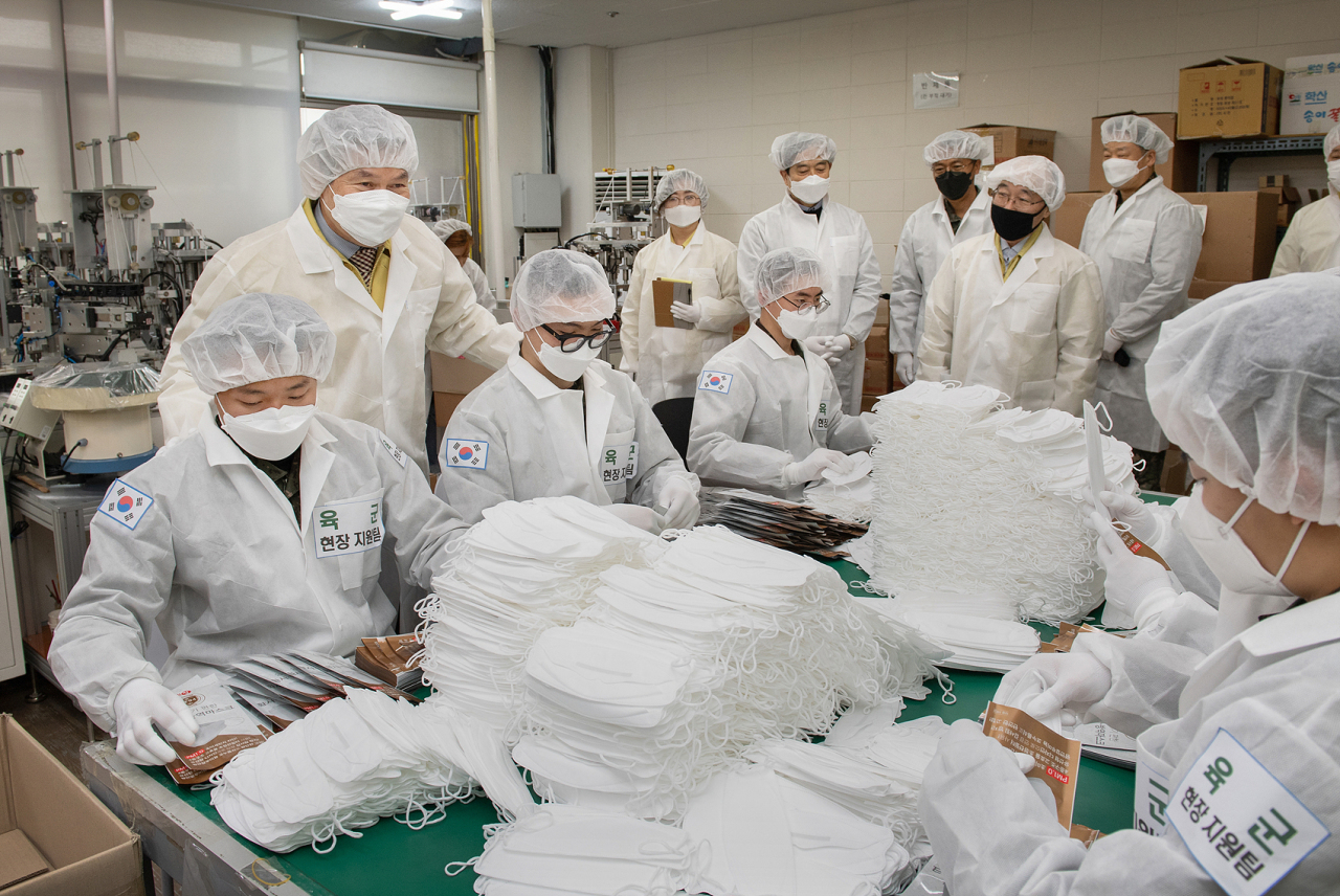 Soldiers package protective masks at a factory in southern Gyeonggi Province on Saturday. During a visit to the factory, Defense Minister Jeong Kyeong-doo thanks the soldiers and vows to exhaust all avenues to stop the COVID-19 epidemic. (Ministry of National Defense)