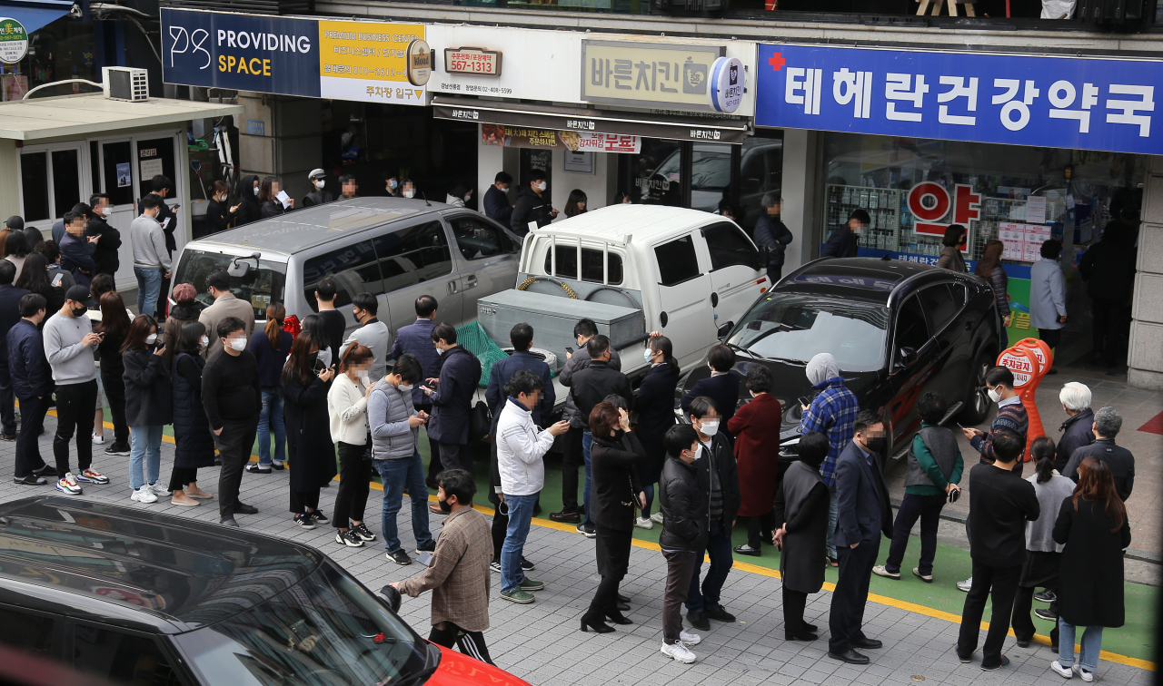 People line up to buy face masks, considered essential as a precaution against the new coronavirus, in front of a pharmacy in central Seoul on Monday, as the nation introduces a new distribution system to ease the acute supply shortage. Yonhap