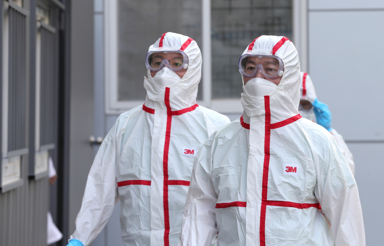 Ahn Cheol-soo (right) is seen in full protective gear at Daegu Dongsan Hospital in the coronavirus-hit city of Daegu, where he has volunteered to join the medical team treating COVID-19 patients, on March 2. (Yonhap)