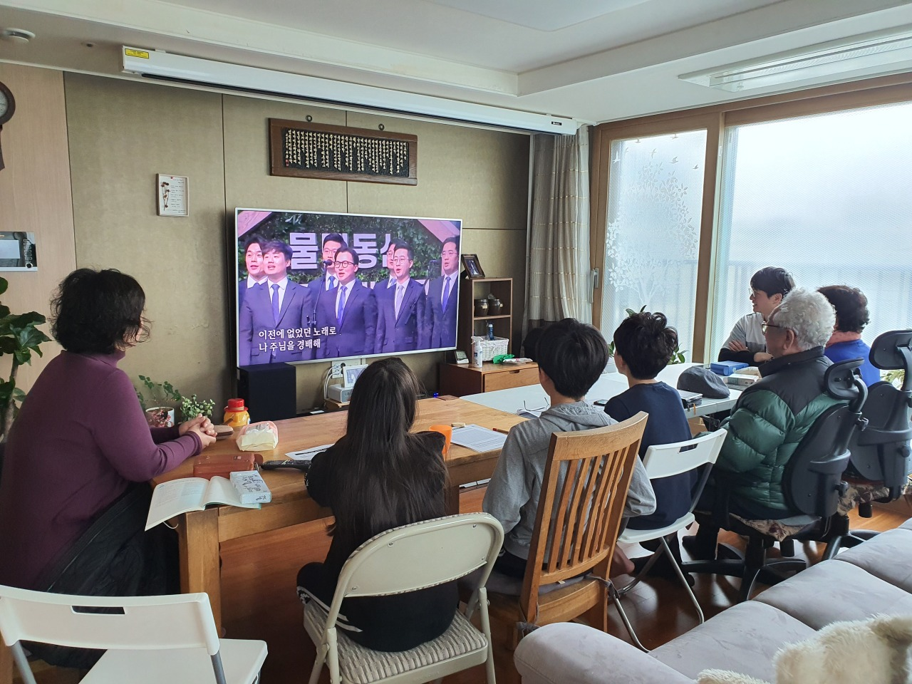 Family gathers in a living room on Sunday for the online Sunday service. (Sarang Church)
