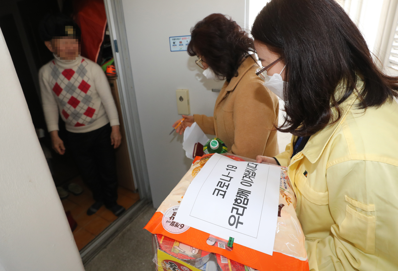 A civil servant and welfare officer deliver food and face masks to an elderly citizen at an apartment in Buk-gu, Gwangju, Feb. 4. (Yonhap)