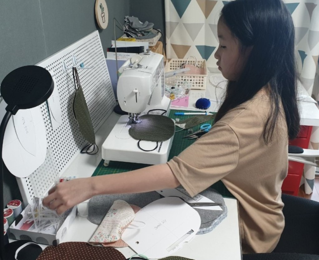 Park Jin-ryoung's daughter Yoo-jin helps her make face masks at home on a sewing machine. (Provided by Park Jin-ryoung)