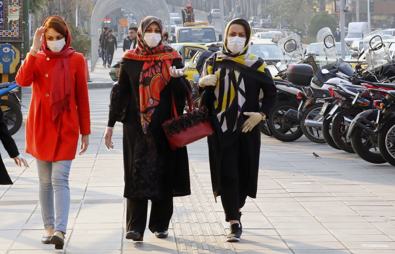 Iranians wearing face masks and protective gloves go shopping in a bazaar during the coronavirus pandemic in Tehran, Iran, March 12. (EPA-Yonhap)