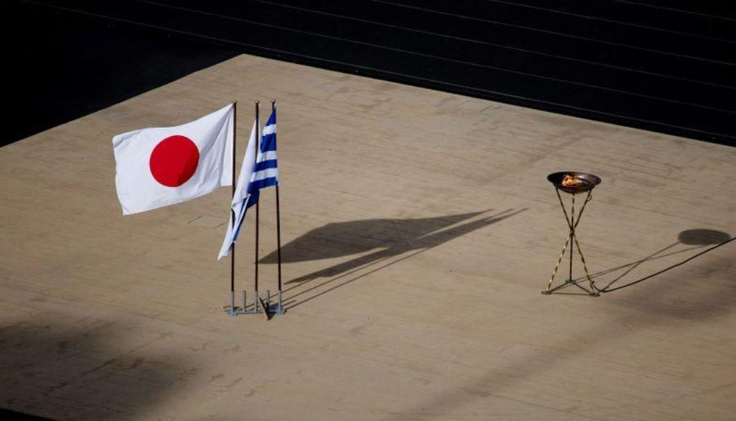 The Japanese national flag waves next to an altar with the Olympic flame of the Tokyo 2020 Summer Olympics, following the cancellation of the torch relay as a precaution against the spread of the coronavirus (Reuters)
