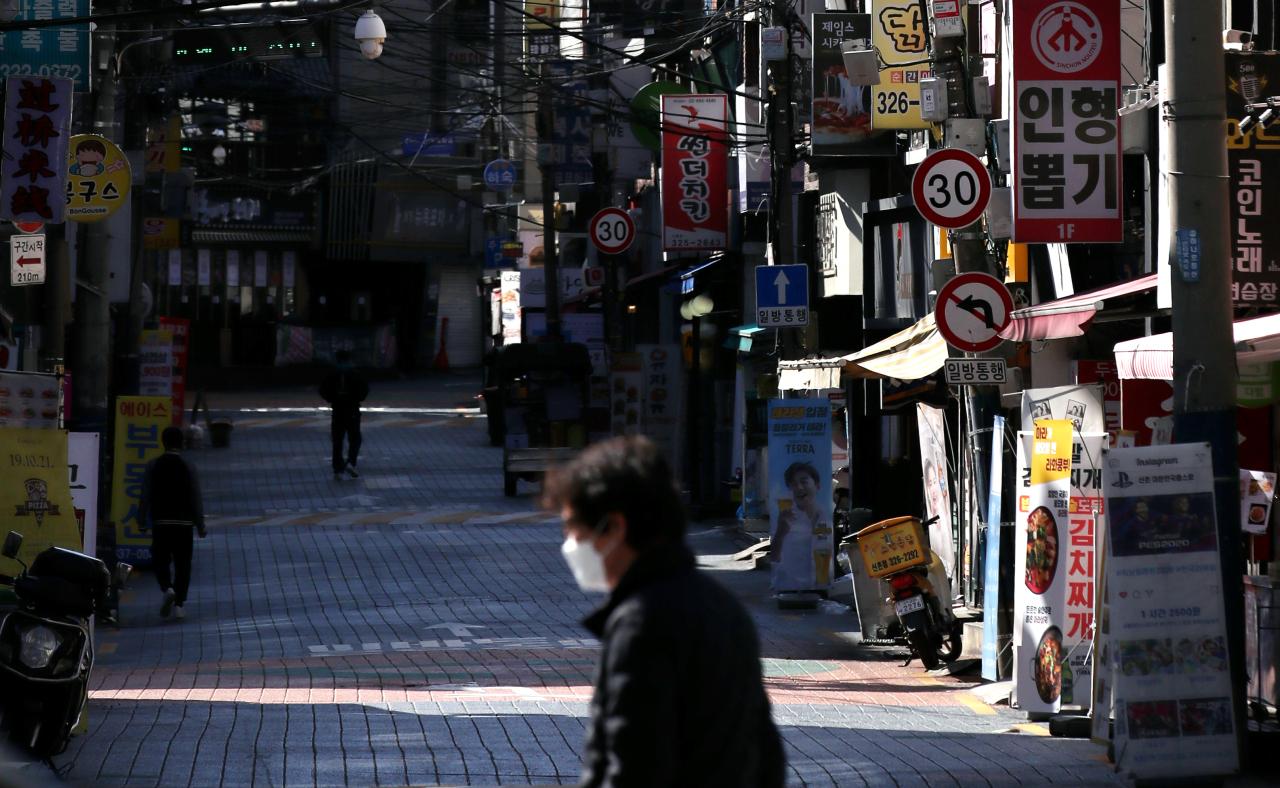 A passerby walks down an empty street in Sinchon, a popular university district in Seoul. (Yonhap)