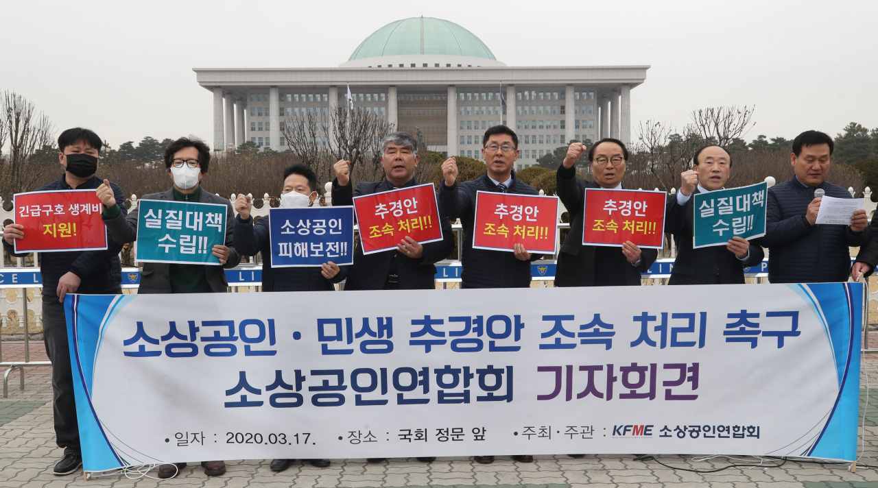 Members of Korea Federation of Micro Enterprise hold signs demanding the government's financial support for small business owners, in front of the National Assembly in Seoul on Tuesday. (Yonhap)