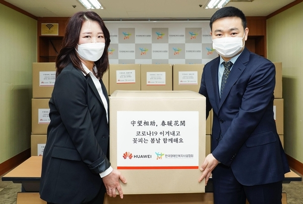Huawei Korea CEO Shawn Meng (right) delivers face masks to the Korea Association of Welfare Institutions for Persons with Disabilities on Friday. (Huawei Korea)