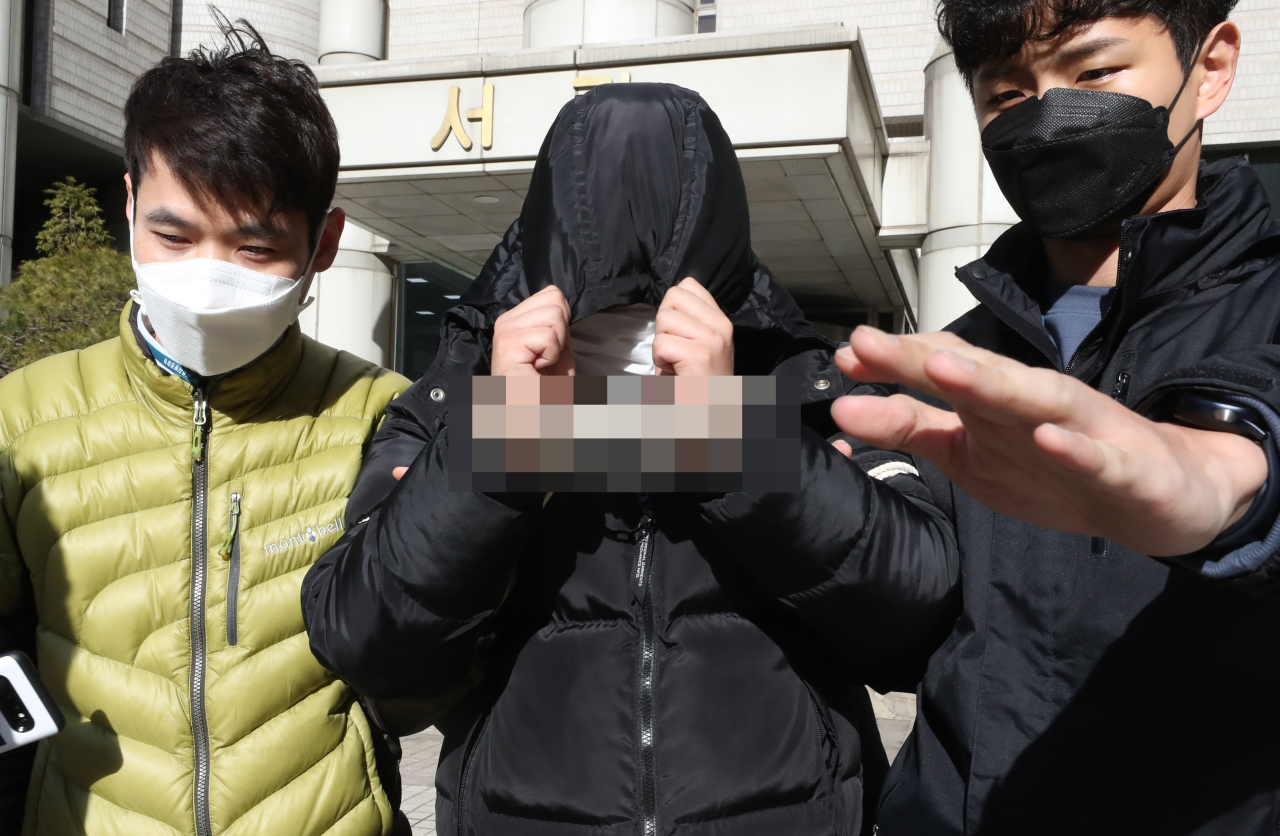 Suspect Cho (center) hides his face as he leaves the Seoul Central District Court on Thursday. Yonhap