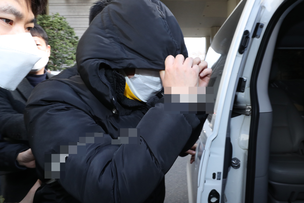 Suspect Cho hides his face as he leaves the Seoul Central District Court on Thursday. Yonhap