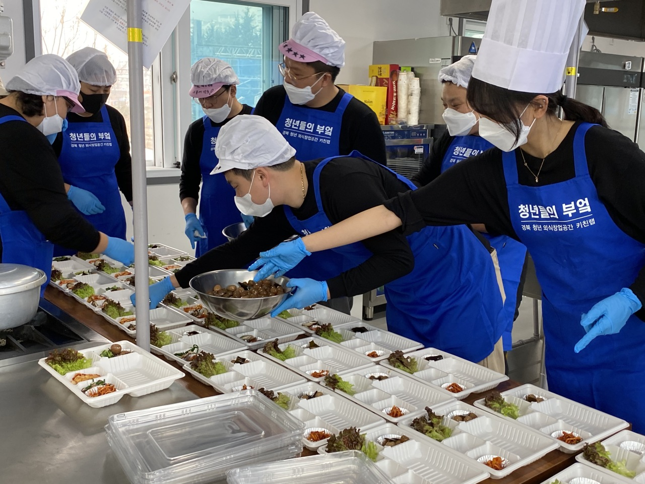 Volunteers prepare packaged meals for those working on the front lines of the coronavirus fight, including hospitals and testing sites, in Gyeongsan, North Gyeongsang Province, March 8. (Yonhap)