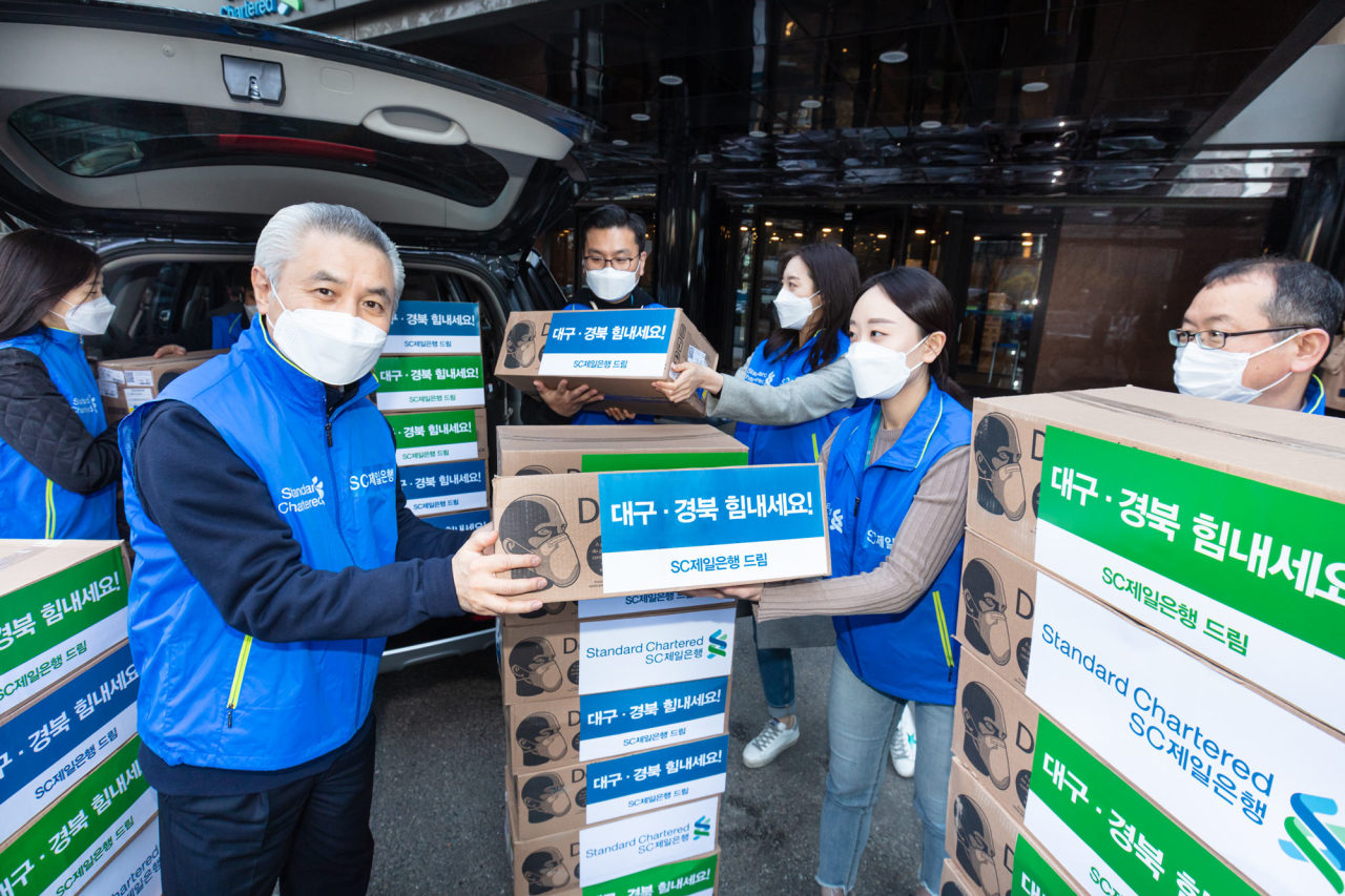Standard Chartered Bank Korea CEO Park Jong-bok (second from left) and employees load 5,000 face masks provided by Standard Chartered PLC onto vehicles to donate them to Keimyung University Dongsan Medical Center in Daegu on Monday. (SC Bank Korea)