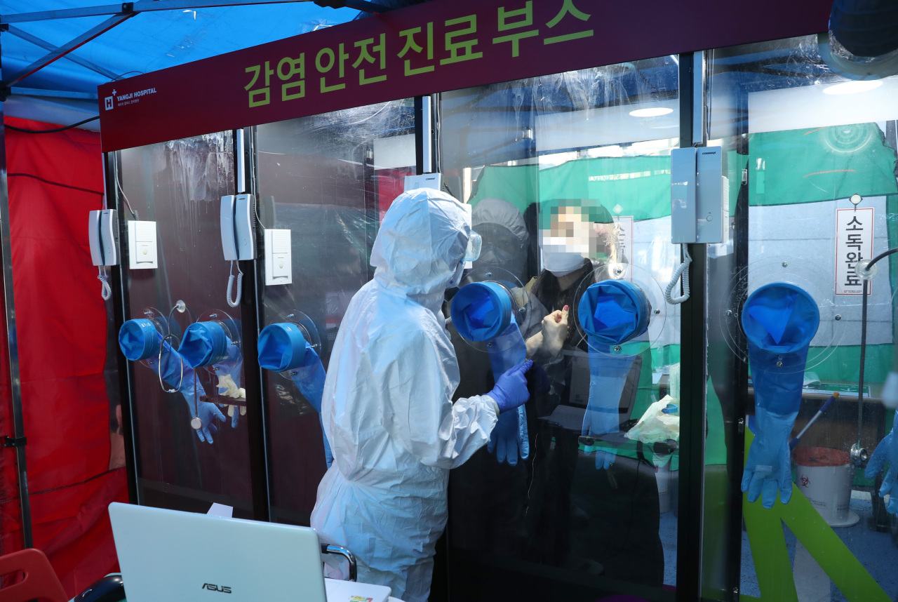 Medical staff take samples at a one-person booth set up at H-plus Yangji Hospital in Gwanak-gu, Seoul, March 16. The booth is designed to minimize contact during testing for COVID-19 infection. (Yonhap)