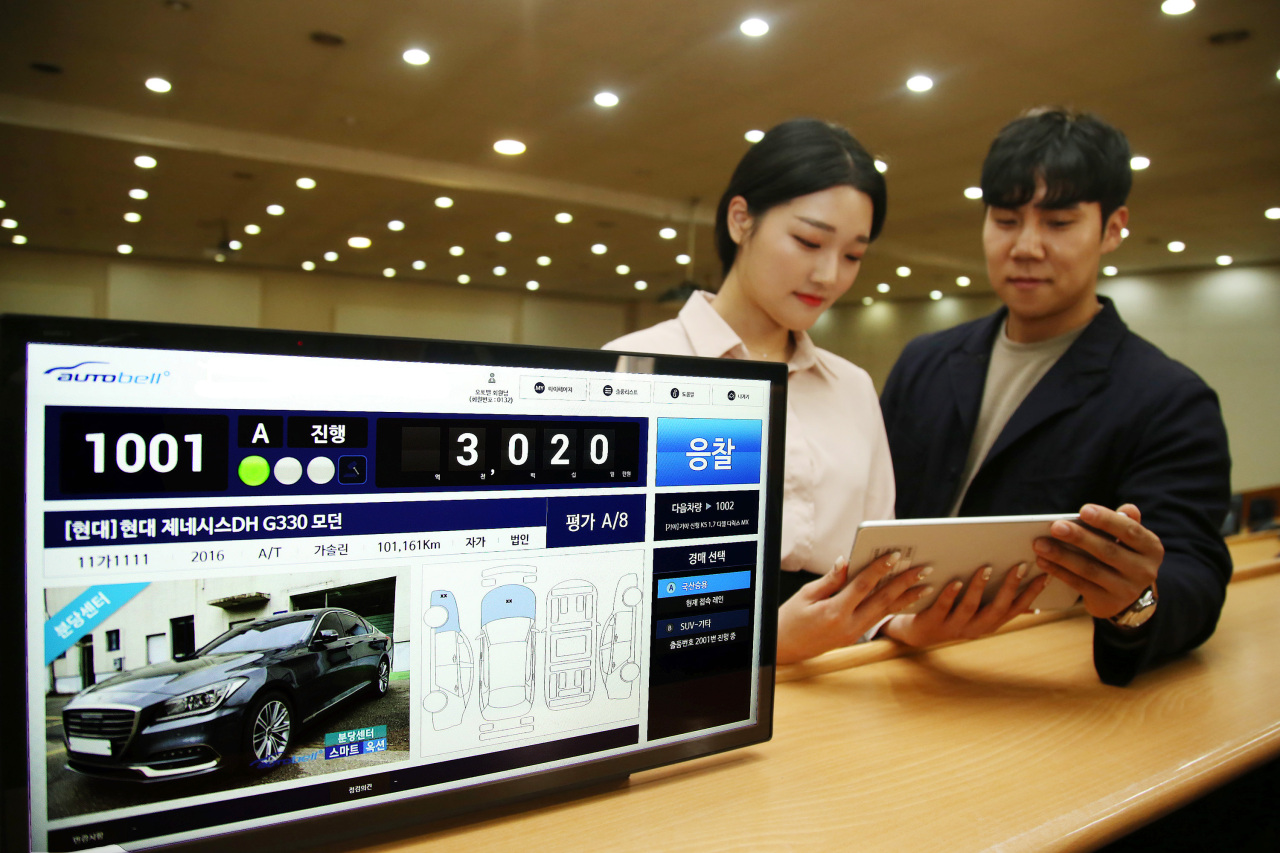 Hyundai Glovis officials test Autobell smart auction system via a mobile device at its Bundang used car auction center in Gyeonggi Province. (Hyundai Glovis)