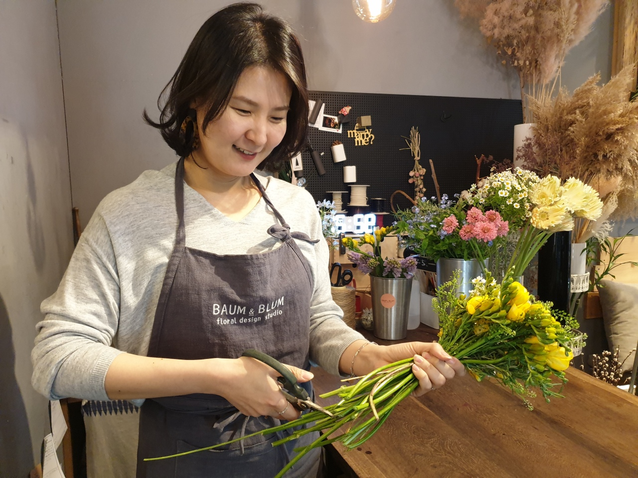 Florist Lee Se-been trims geraniums at Zien Shop in Yongin, Gyeonggi province. (Park Yuna/ The Korea Herald)