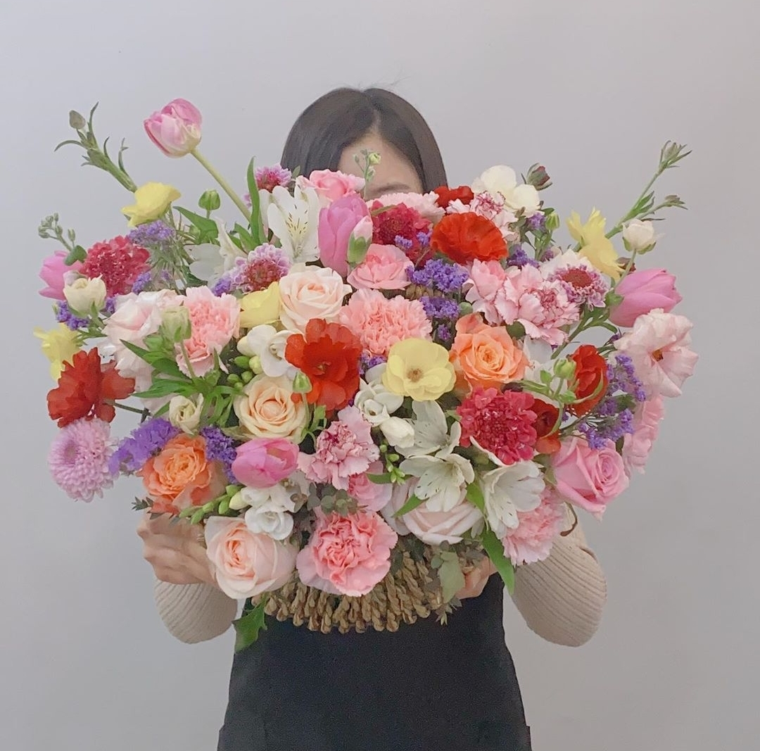 Florist Park Hyun-jin holds up a basket of flowers that includes yellow and red Ranunculus Butterfly. (Provided by Park Hyun-jin)