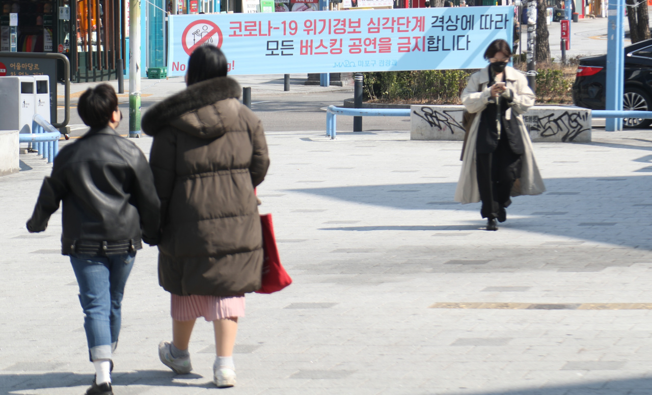 A banner that says all busking performances are banned due to the raised virus alert is seen in the Hongdae area in western Seoul on March 8. (Yonhap)
