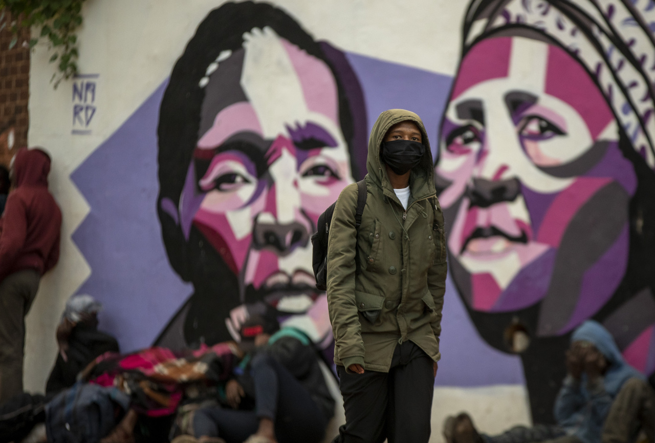 A man wearing face masks to protect herself against coronavirus, walks on the street in Hillbrow, Johannesburg, South Africa, Friday. South Africa went into a nationwide lockdown for 21 days in an effort to mitigate the spread to the coronavirus. (AP)