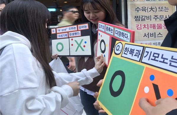 "The Korean Culture and Information Service's 10th group of ""Friends of Korea"" promotes Korean culture on a Seoul street during an outreach activity last year. (KOCIS)"