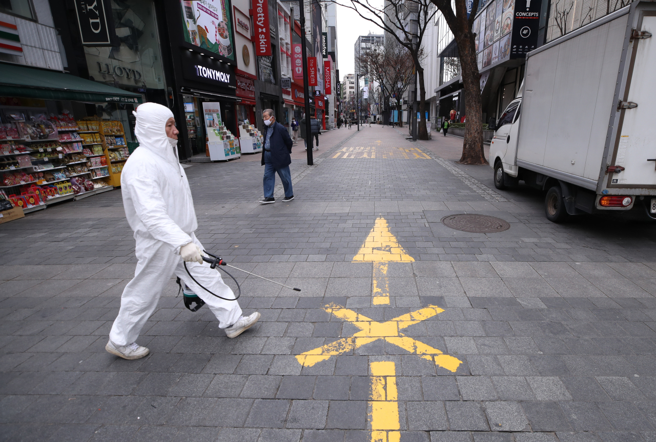 An official from the Jung-gu District Office takes a disinfectant equipment across an empty street in Myeongdong, central Seoul. (Yonhap)