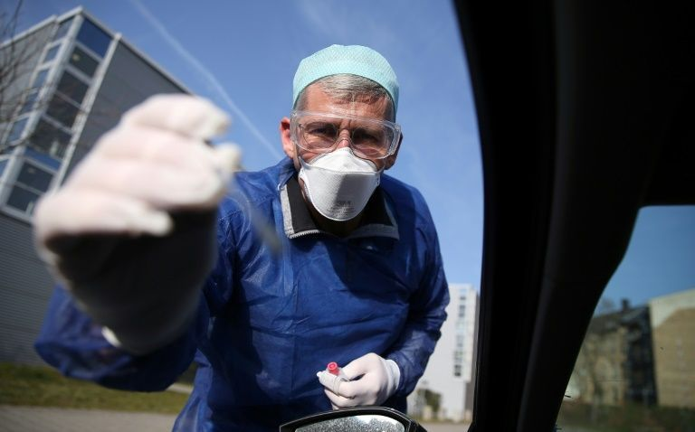 German doctor Michael Grosse takes a sample from a car driver at a drive-through testing point for the coronavirus in Halle, eastern Germany (AFP)