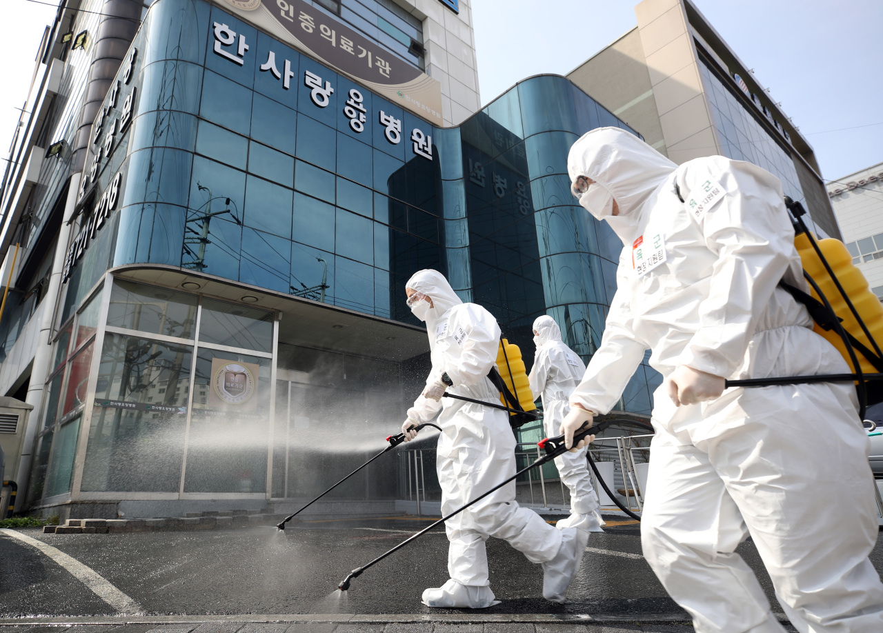 South Korean soldiers wearing protective gear sanitize a street in front of a hospital in Daegu on Monday. (Yonhap)