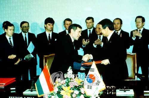 This file photo, taken Feb. 10, 1989, shows then South Korean Foreign Minister Choi Ho-joong (right) shaking hands with his Hungarian counterpart, Gyula Horn, after establishing the two countries` diplomatic relations. (Yonhap)