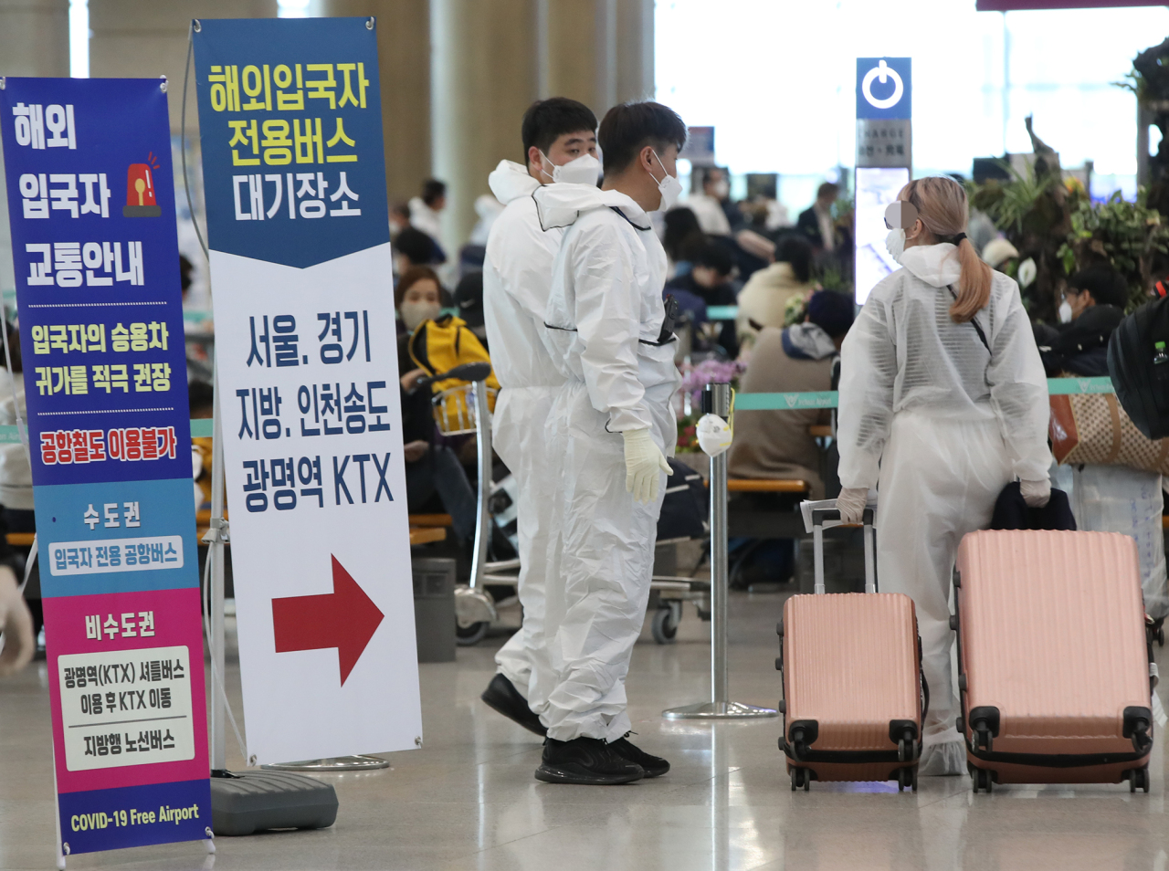 Quarantine officials direct travellers arriving from overseas to designated bus stop at the Incheon International Airport on Wednesday. Yonhap