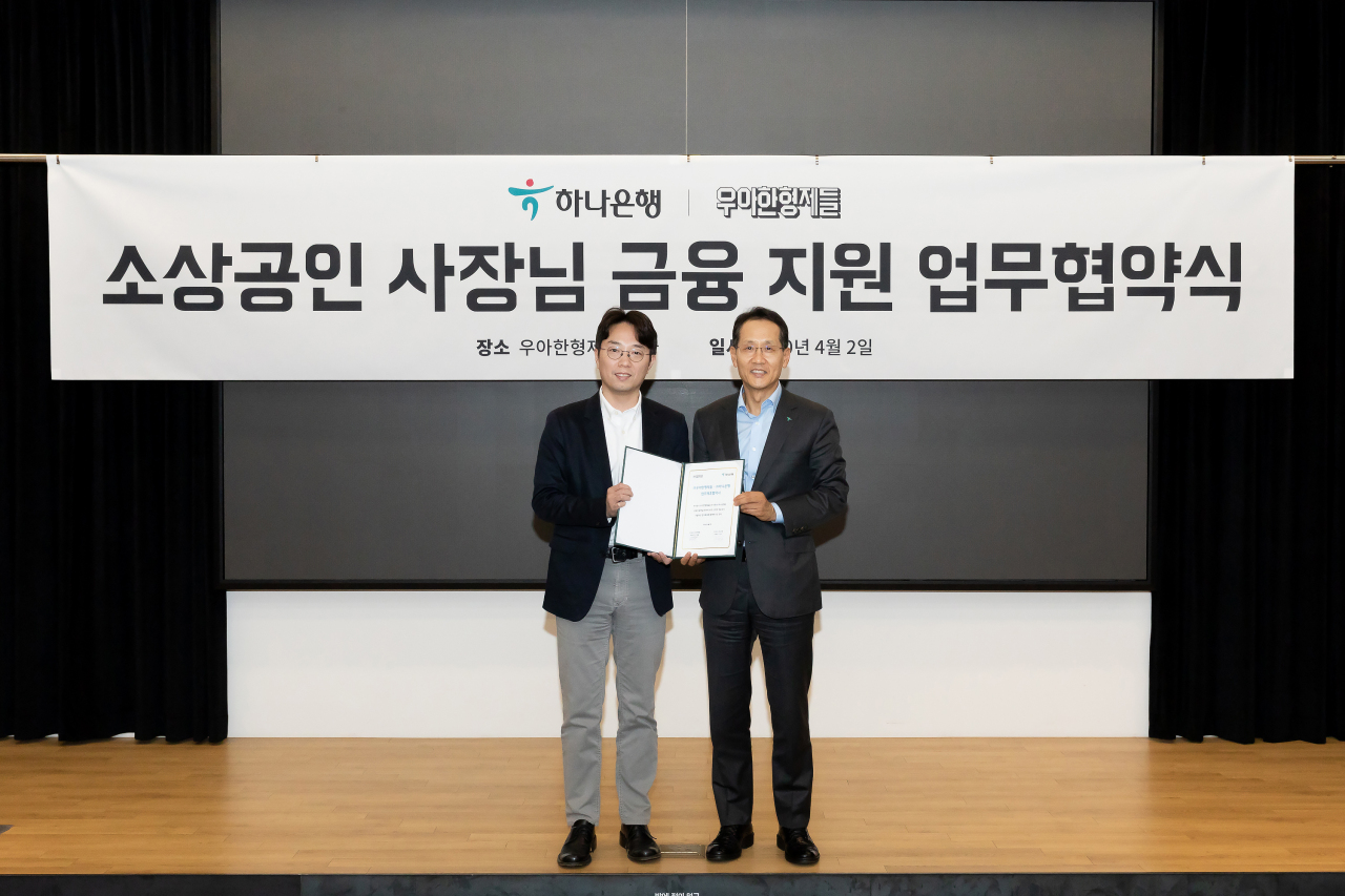 Woowa Brothers CEO Kim Beom-jun (left) and Hana Bank CEO Ji Sung-kyu pose for a photo at a ceremony for a memorandum of understanding on Thursday at Woowa Brothers headquarters in Seoul. (Woowa Brothers)