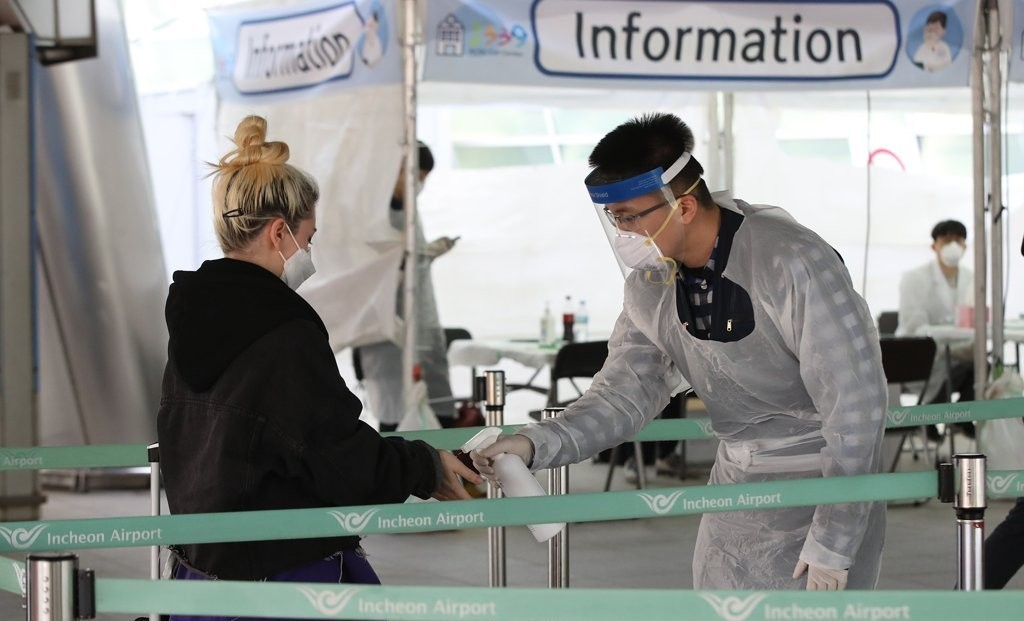 A tourist from Europe undergoes a COVID-19 test at a temporary walk-through test center outside Incheon International Airport, west of Seoul, on March 31, 2020. (Yonhap)