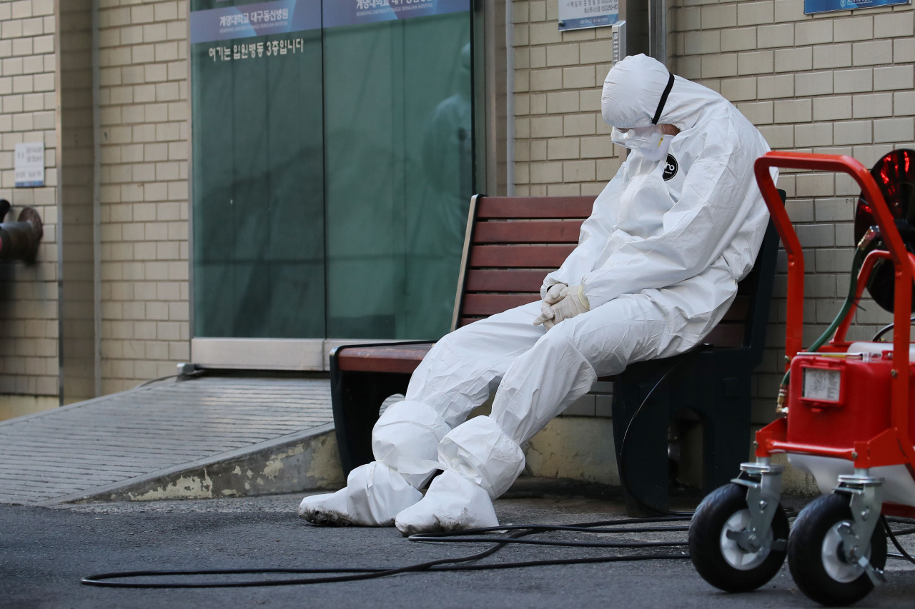 A health care worker sits outside a hospital in Daegu. (Yonhap)