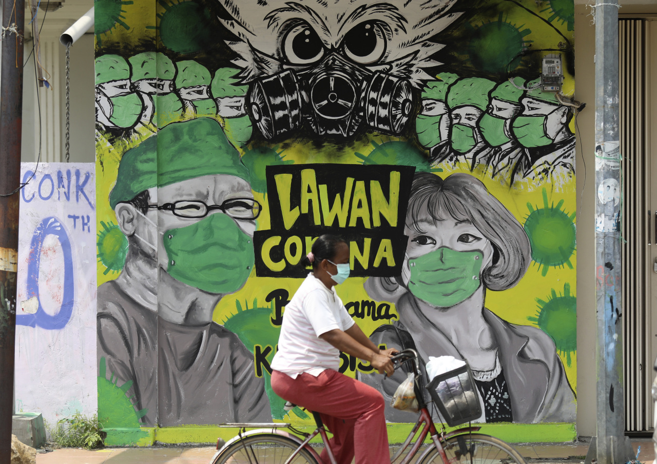 A woman rides her bicycle past a coronavirus awareness mural depicting medical workers in Bangkalan, Madura Island, Indonesia, Monda. (yonhap)