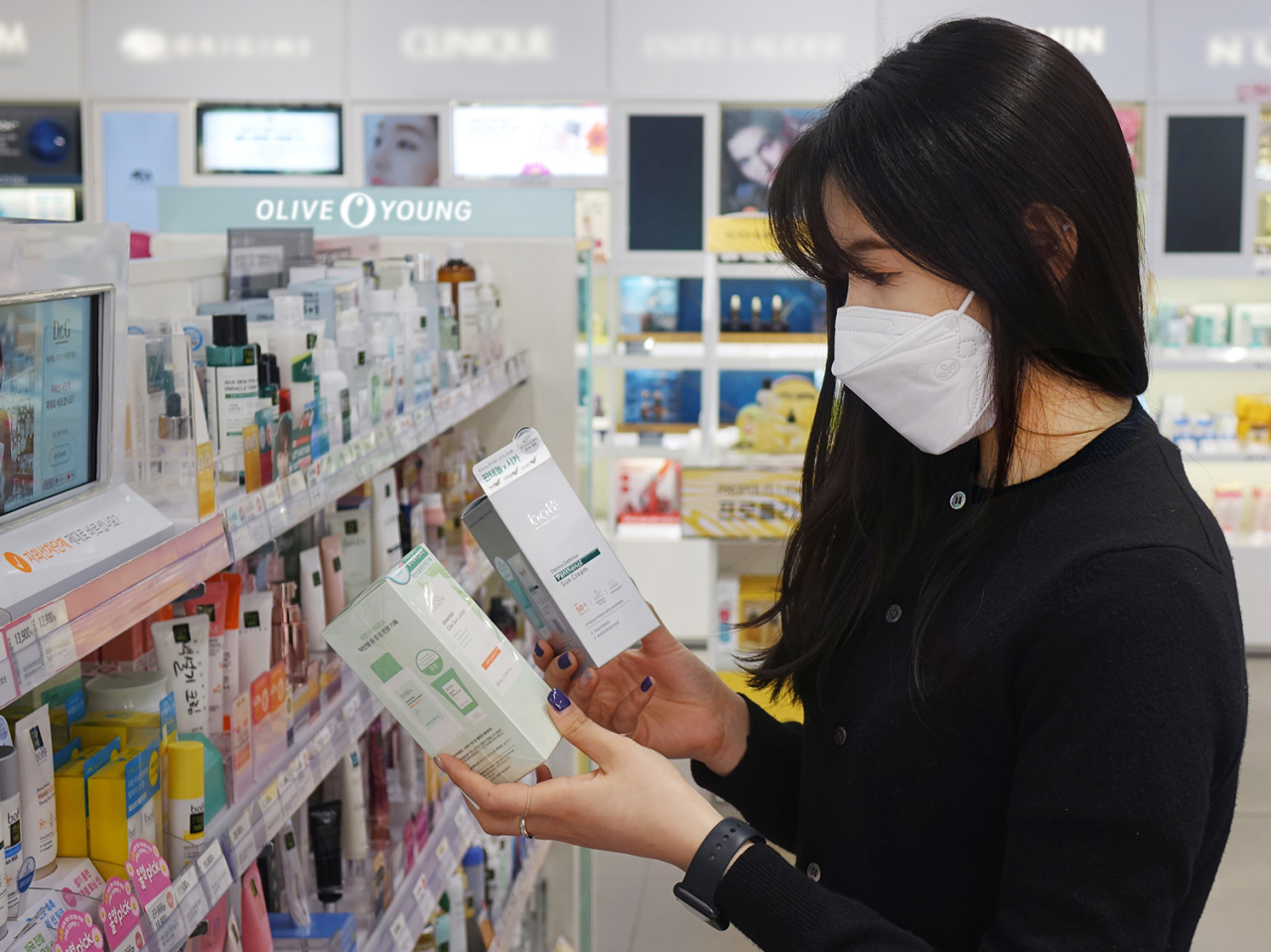 A masked customer looks at a sunscreen product. (CJ Olive Young)