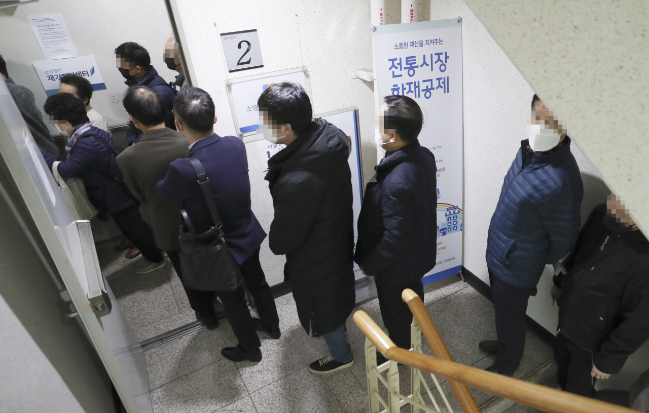 Small business owners wait in line to apply for emergency rescue loans at the Seoul Central Center of the Small Enterprise and Market Service on March 24. (Yonhap)