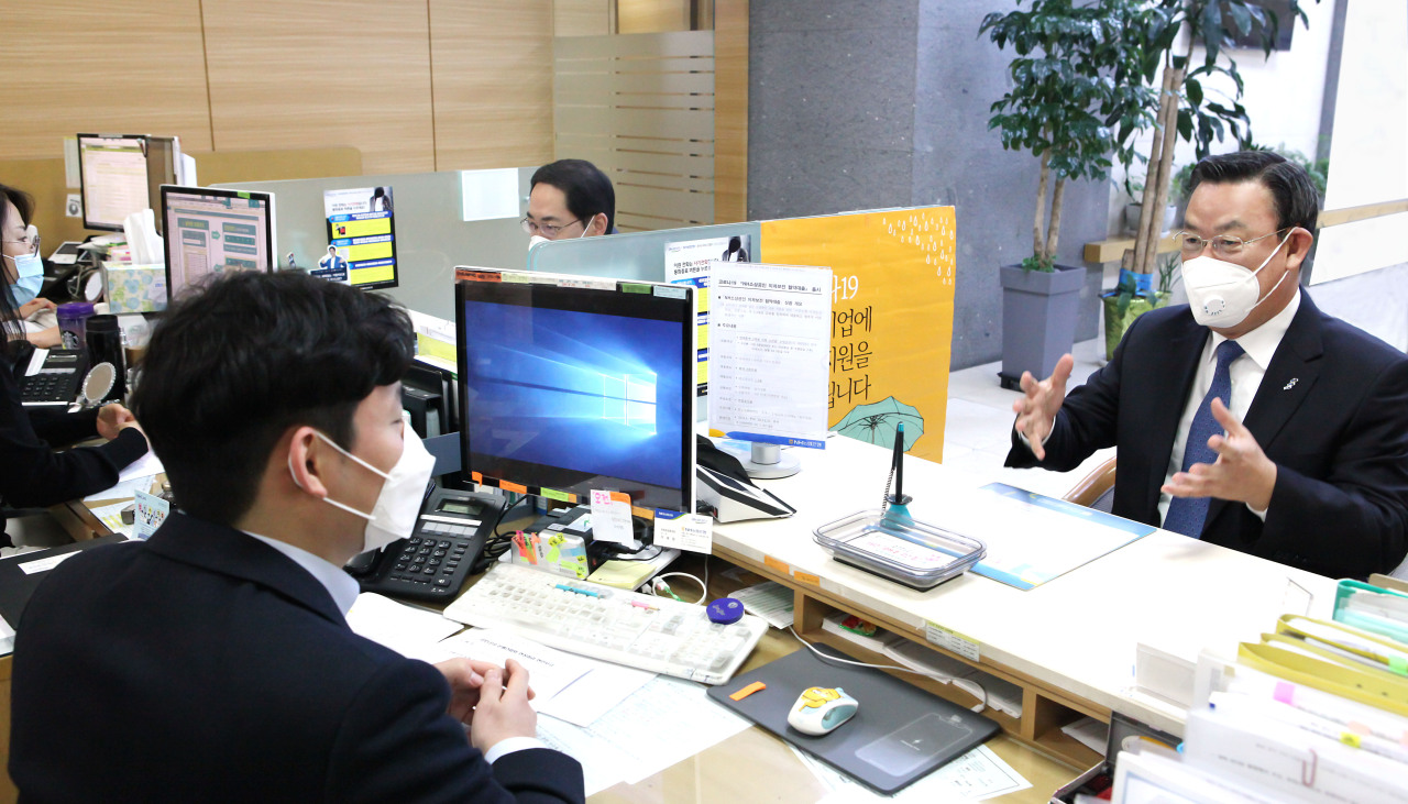 Korea Federation of Banks Chairman Kim Tae-young discusses the topic of extending loans to small businesses with a NH Nonghyup Bank employee in central Seoul on April 2. (Yonhap)