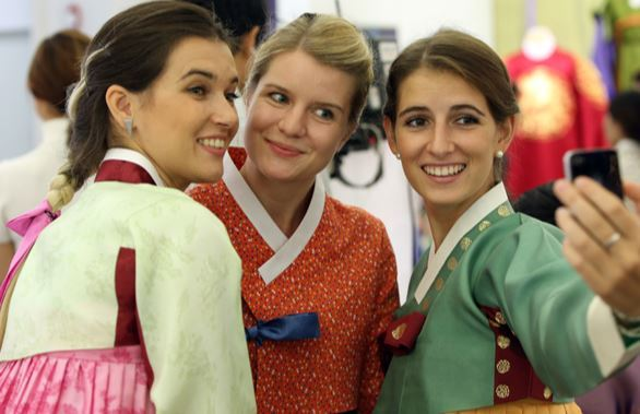 """Foreign students take part in a hands-on """"hanbok"""" festival, where they had a chance to try on Korea's traditional costume, in downtown Seoul. (Yonhap)"""