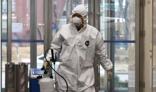 A health worker wearing a protective suit enters the Ministry of Personnel Management in Sejong City, 130 kilometers south of Seoul, on Feb. 28, 2020, after an employee tested positive for the novel coronavirus. (Yonhap)