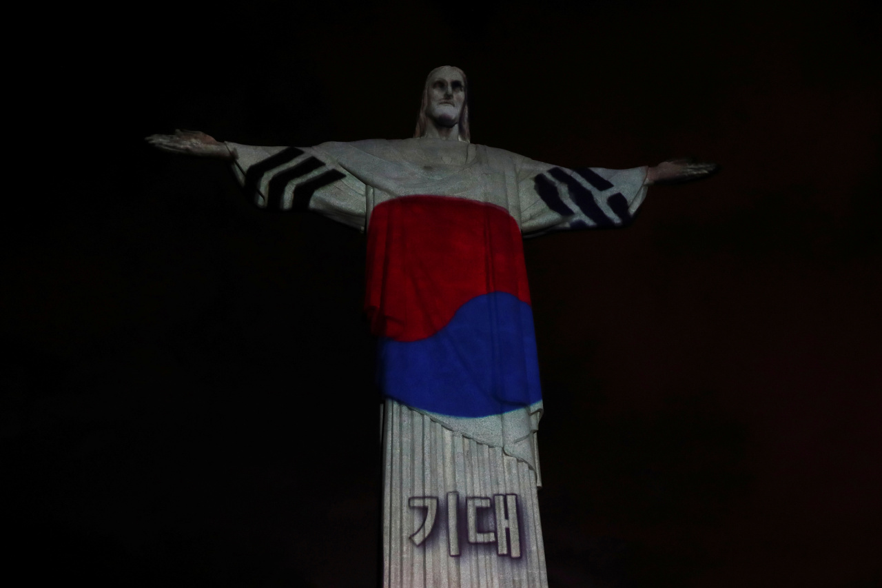"""The statue of Christ the Redeemer is lit up in the colors of the South Korean flag during Easter Sunday events, amid the COVID-19 outbreak, in Rio de Janeiro. The word projected on the statue reads """"Hope."""" (Reuters)"""