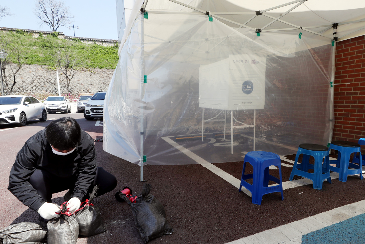 Election officials set up a special polling booth outside a polling station in Incheon, exclusively for voters who are quarantined for possible COVID-19 infection on Tuesday, prior to Wednesday's parliamentary elections. (Yonhap)