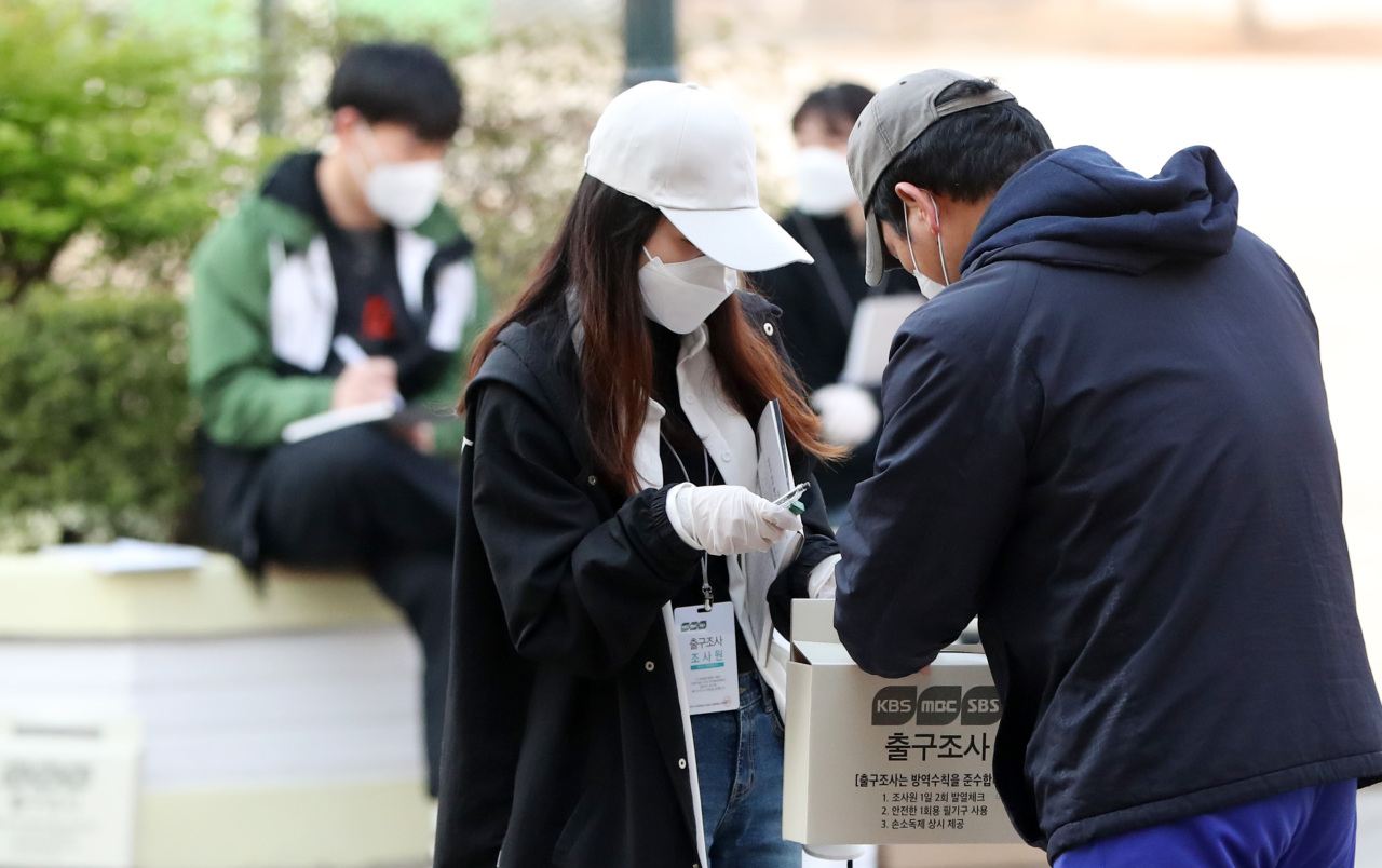 A voter accepts an exit poll request outside a polling station in Seoul. (Yonhap)