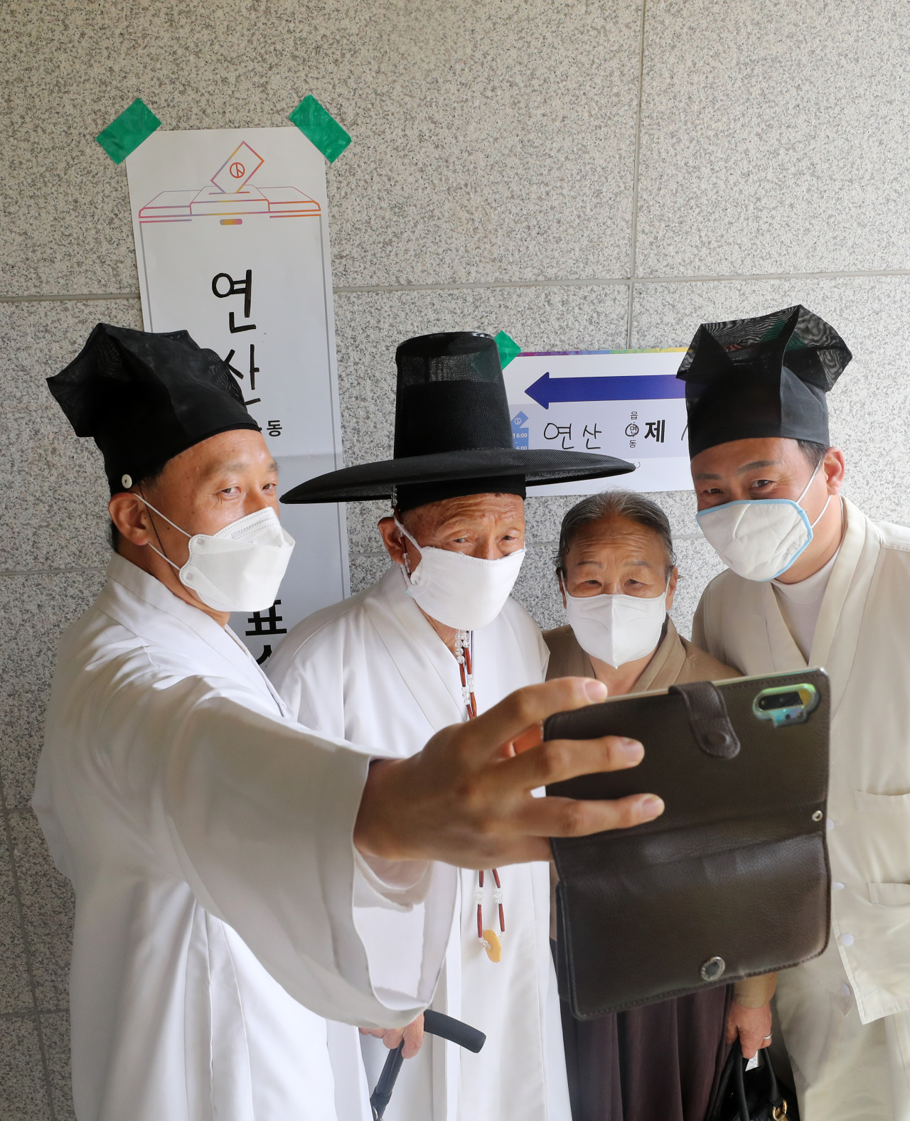 Yoo Bok-yeop (second from left), a senior teacher at Yangji Village School, and their family photograph themselves after casting their ballots in Nonsan, South Chungcheong Province, Wednesday. (Yonhap)