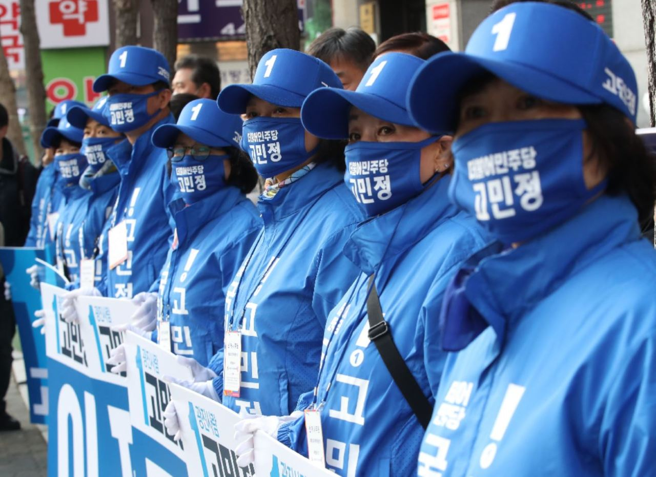 Campaigners for a candidate from the ruling Democratic Party of Korea cover their faces with masks that have the candidate's name on them. (Yonhap)