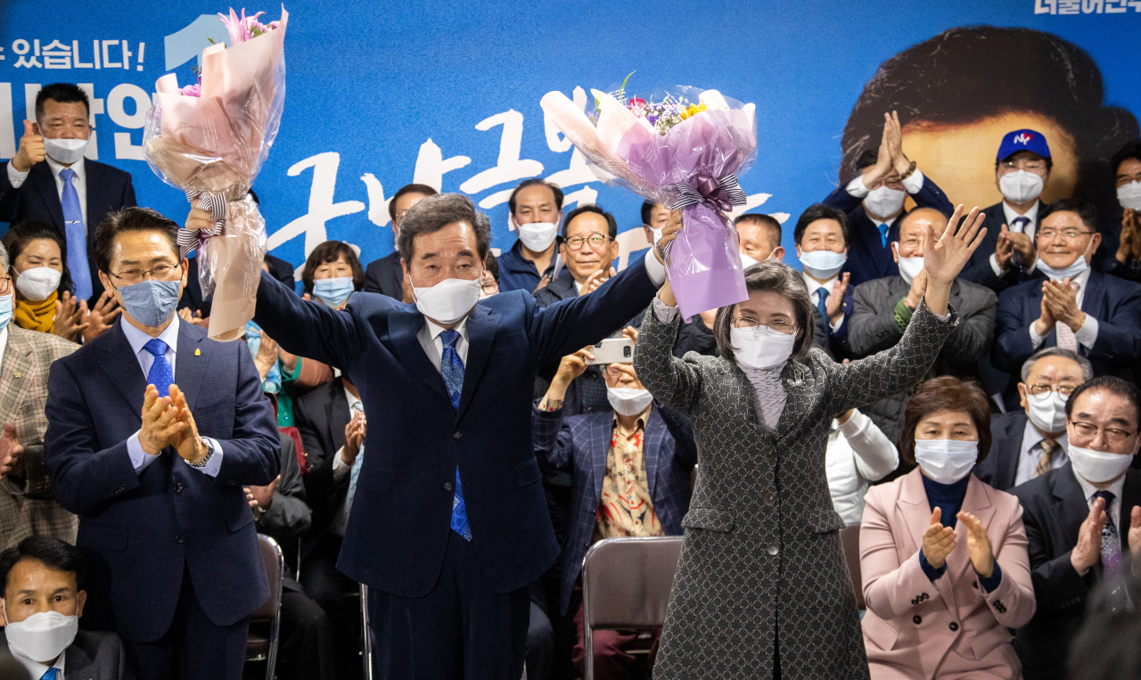 Former Prime Minister Lee Nak-yon, a candidate of the ruling Democratic Party in the general elections, holds up a boquet after he was certain to secure victory in the Jongno constituency in Seoul on Wednesday. (Yonhap)