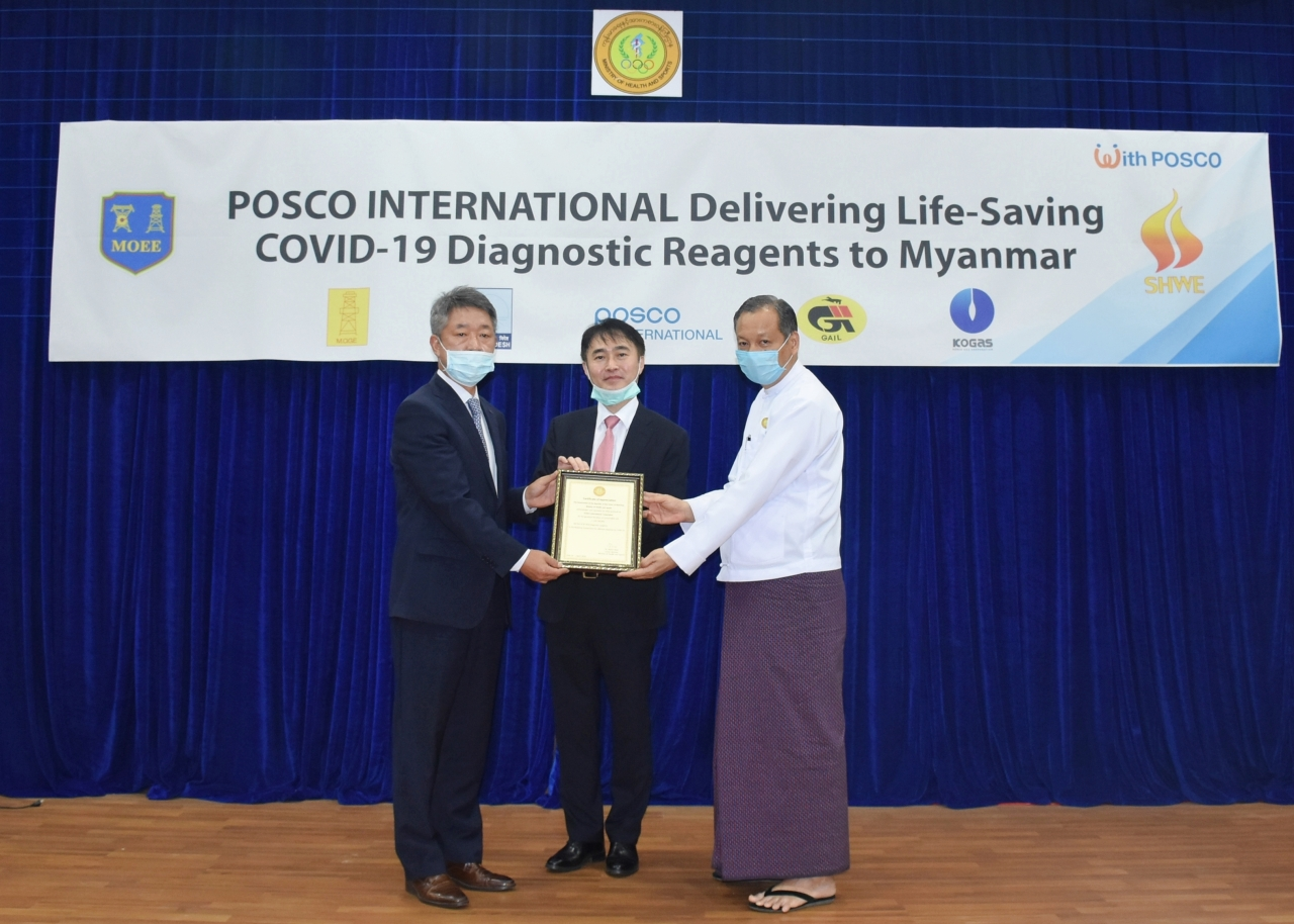 Zaw Than Htun, director general of Myanmar's Medical Research Center (right), Lee Sang-hwa, South Korea's ambassador to Myanmar (center), and Lee Sang-hoon, the regional managing director of Posco International, pose in Myanmar on Saturday. (Posco International)