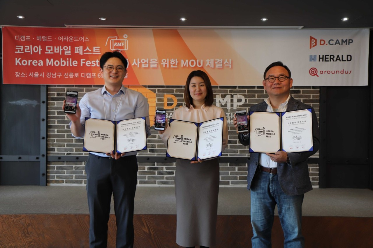 From left: Aroundus CEO Kim Daniel Sung-jin, Herald's New Business Development Department Director Kim Ji-hyun, and D.Camp President Kim Hong-il pose after signing an MOU on April 14 to launch the Korea Mobile Fest at the D.Camp headquarters in Gangnam, Seoul. (D.Camp)