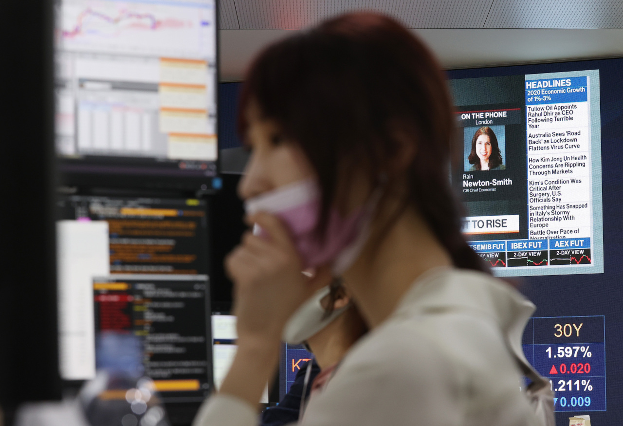 A currency dealer works at KB Kookmin Bank's dealing room in its headquarters in Seoul on Tuesday. (Yonhap)