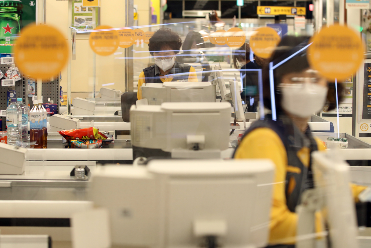 Workers wear face masks at a grocery store in Daegu. (Yonhap)
