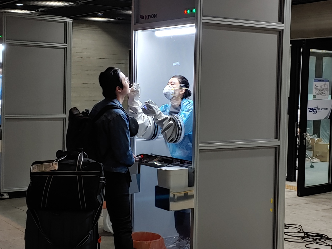 A health care worker conducts nasal swab testing inside the walk-thru testing booth. (Korea Kiyon)