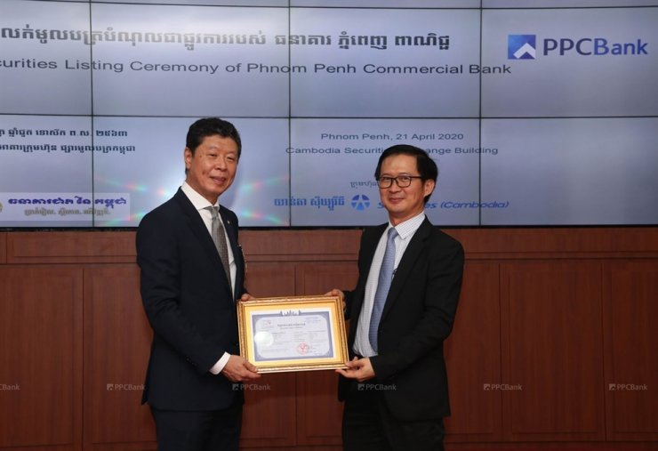 PPC Bank President Shin Chang-moo (left) and CSX CEO Hong Sok Hour pose for a photo with a copy of one of PPC Bank's corporate bonds, at the CSX building in Phnom Penh on April 21. (JB Financial Group)