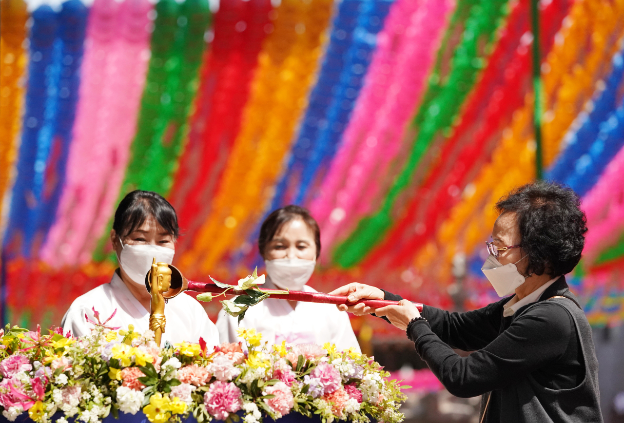 Buddhist followers wearing protective masks attend a service at Joggye Temple in central Seoul on Wednesday. (Yonhap)